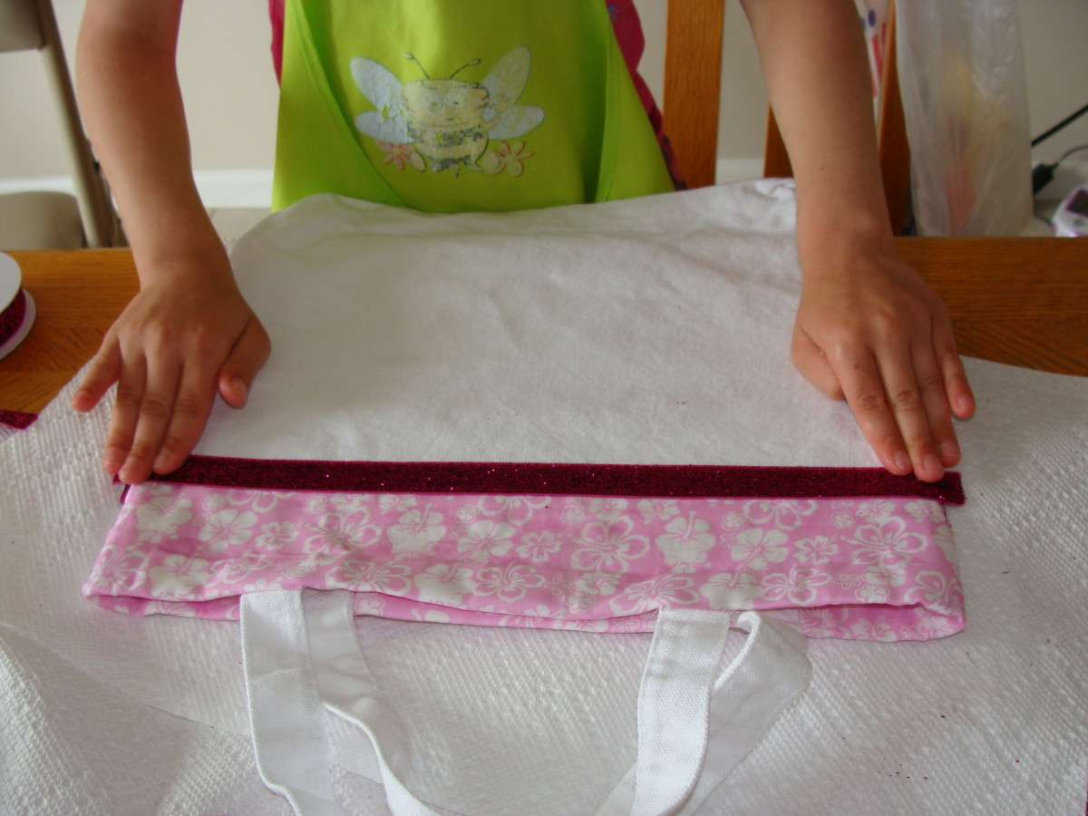 Grace adds her ribbon to the bottom of the fabric border.