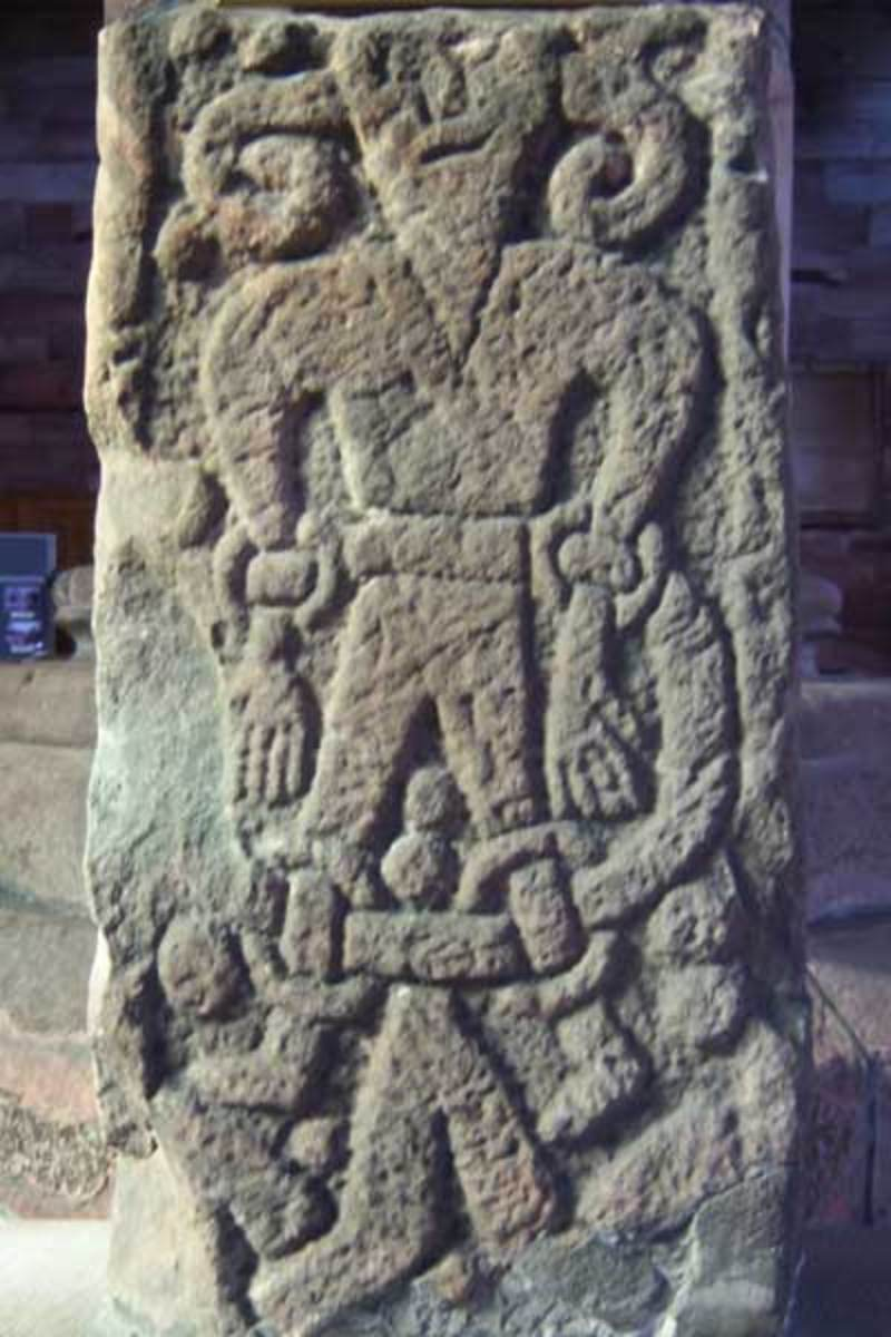 Stone carving of a bound and chained Loki at Kirkby Stephen in eastern Cumbria - he escapes as a salmon only to be caught and chained again, the jaws of his son Jormungand dripping poisonous saliva on his forehead
