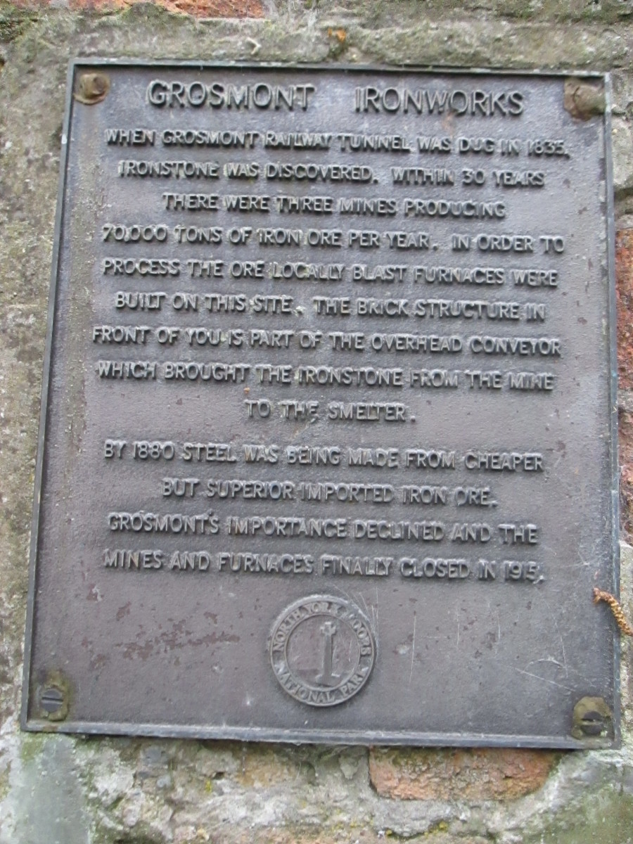 The iron works, commemorated by this plaque,  opened late1830s to process ironstone mined nearby in Eskdale after iron was found during digging the original tunnel bore. The site is north of the line to Whitby