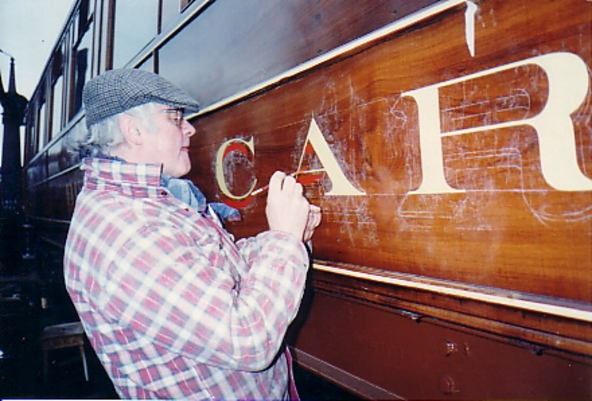 Lettering and numbering is a rewarding, if back-breaking job. A restorer works on a restaurant car waist panel