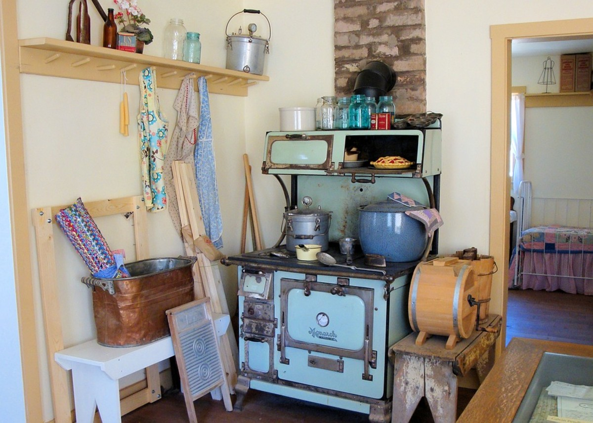 By adding simple elements like vintage aprons, you add a 50's vibe to your kitchen. A cast iron stove helps, too.