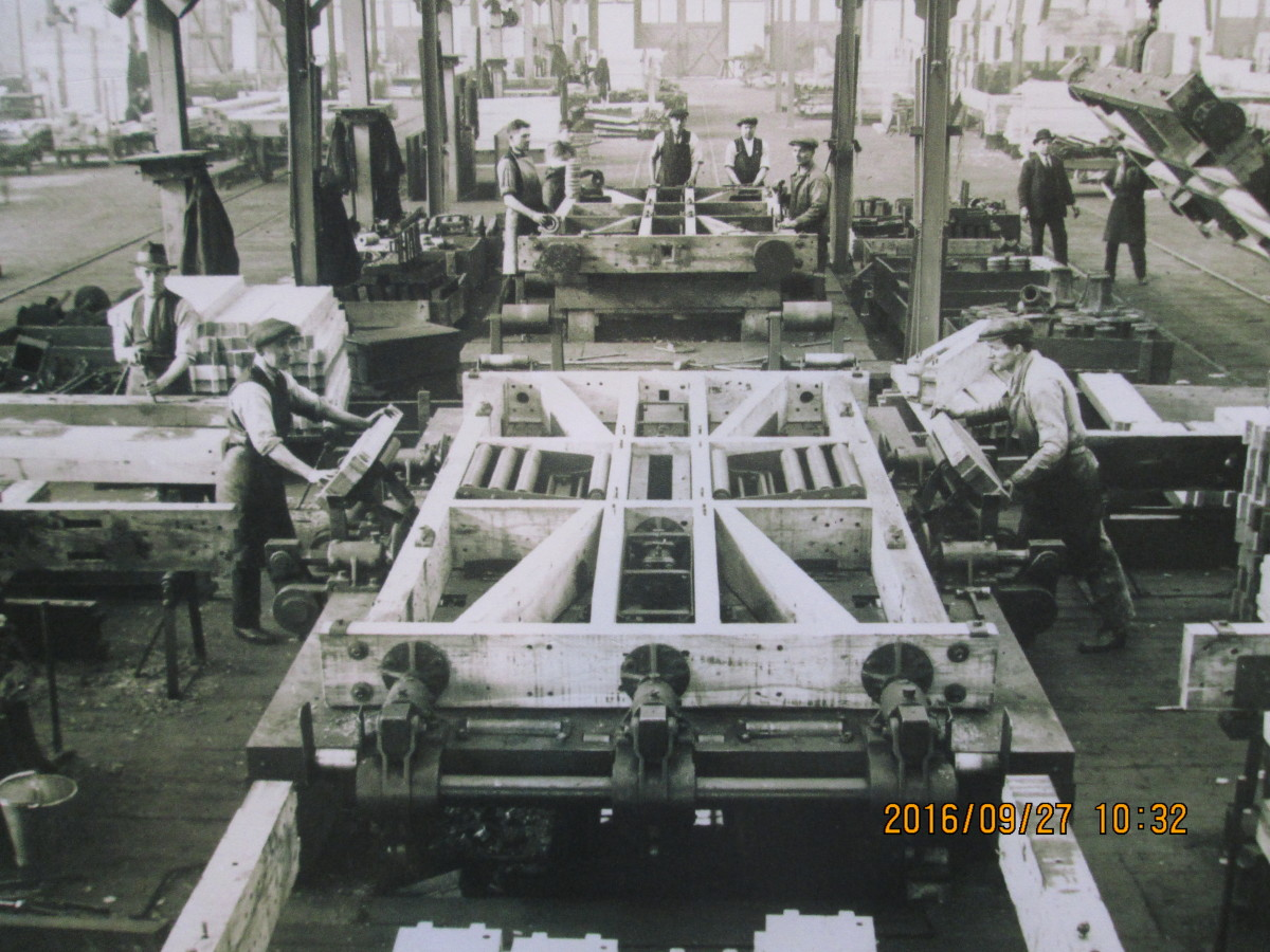 In the wagon workshops, early days - a frame has been assembled, now it has to be tightened. Work goes on apace elsewhere on the suspension, wheels, braking system, couplings, steel cross braces, planking and hinging for doors etc...