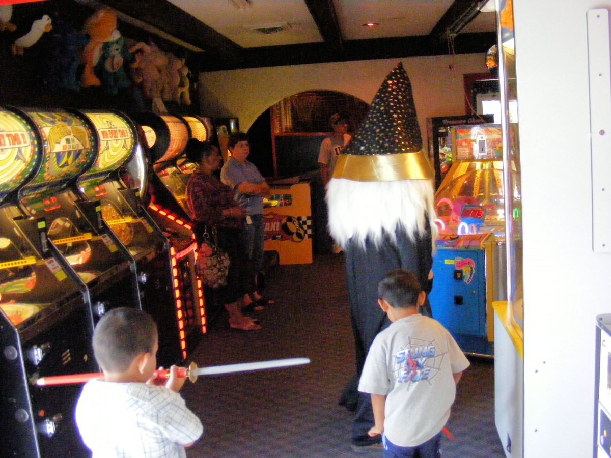A kid threatens the old mascot at the arcade.