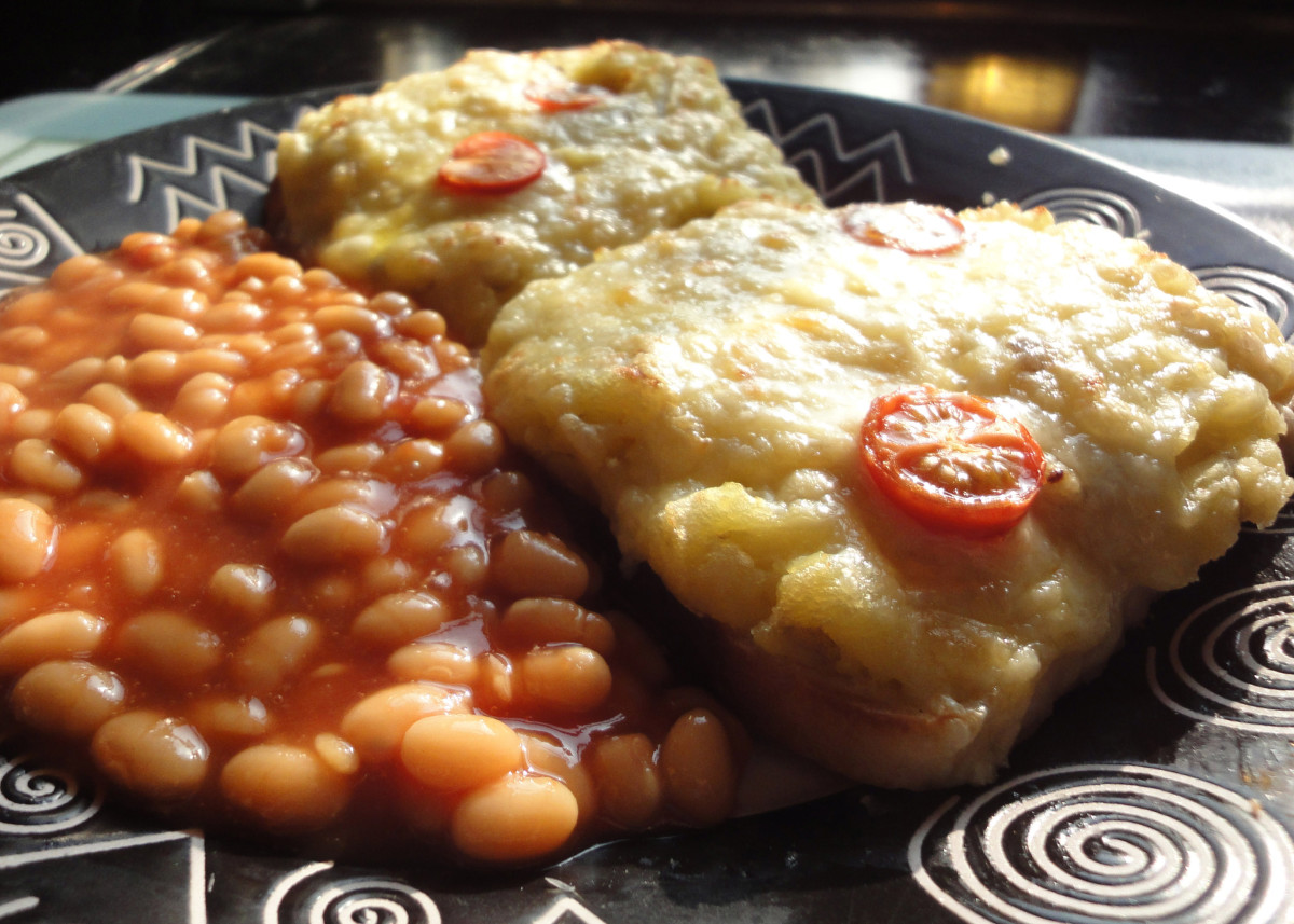Mashed potato on toast topped with grated cheddar cheese and tomato and served with baked beans.
