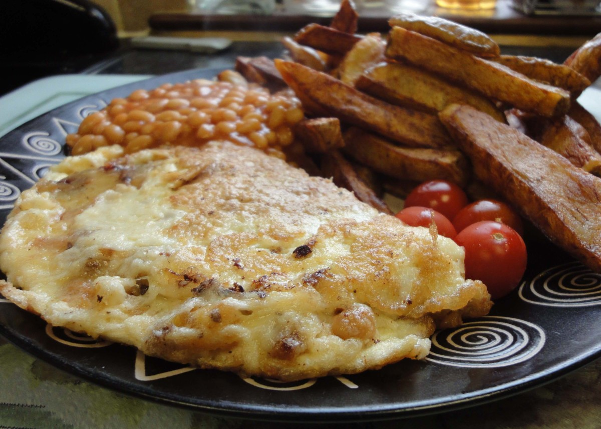 Omelette and chips with baked beans and tomatoes; chips cooked in their skins (potato skins).