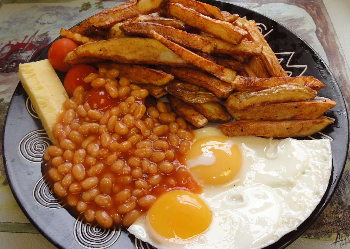 Egg, chips and baked beans with a slice of cheddar cheese; chips cooked in their skins (potato skins).