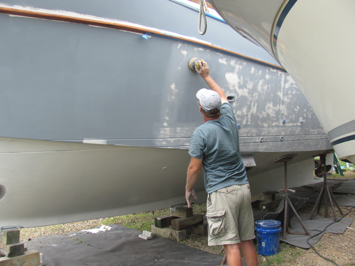Another coat of barrier paint (white) has been applied to the bottom. Luke is still sanding the hull above the waterline smooth to prepare the surface for paint.