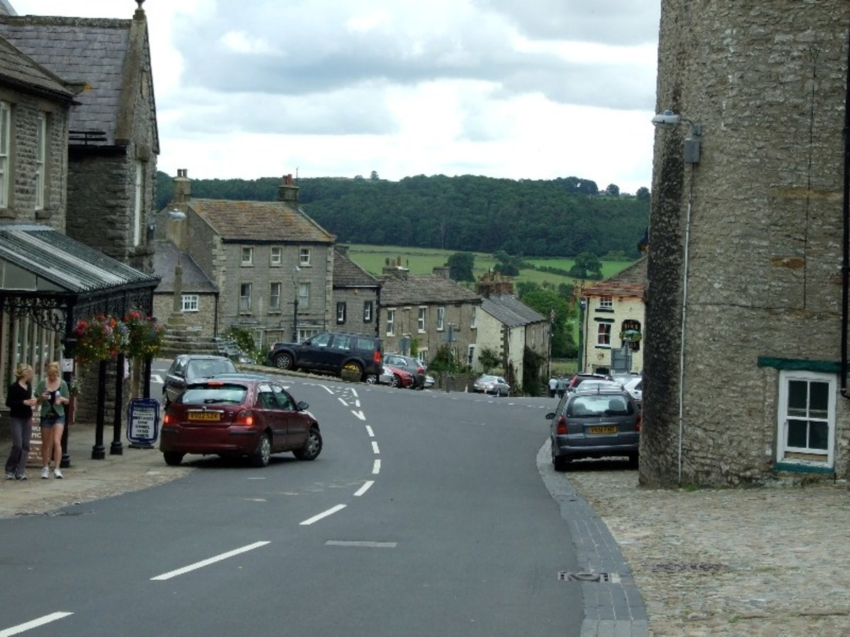 View of the Market Square approaching from the Coverham road. The castle is set back at the right, ahead is the road to Masham, Bedale and Ripon. The road to Leyburn is to the left, downhill to the Ure bridge