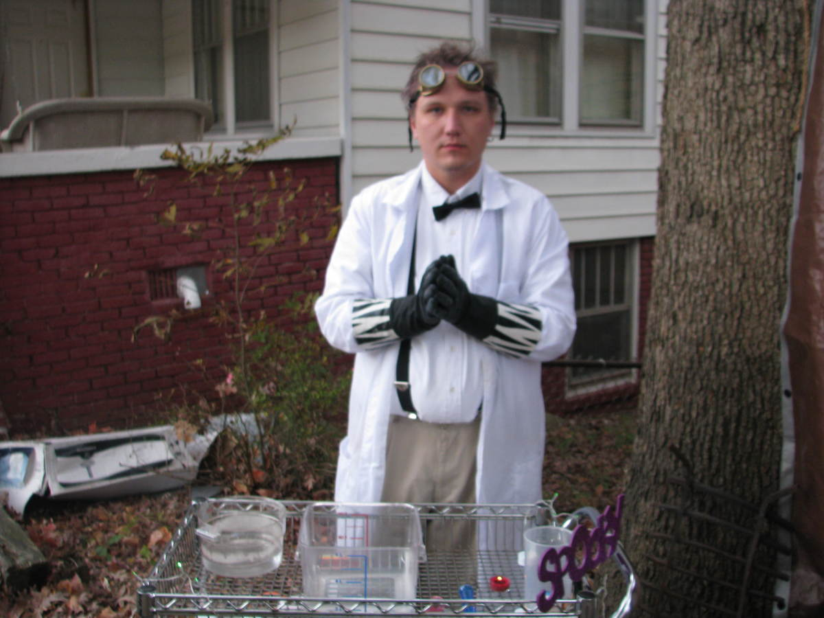 Basic mad scientist costume with lab coat, rubber gloves, goggles, and extra geeky touches with the bow tie and suspenders.