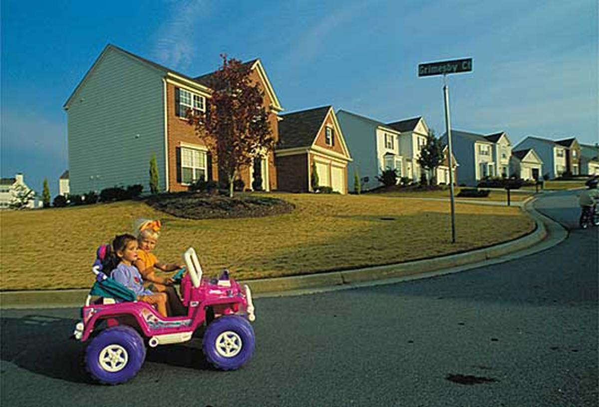 Two girls enjoy the safe and quiet serenity of their neighborhood- taking their Barbie Jeep out for a spin.