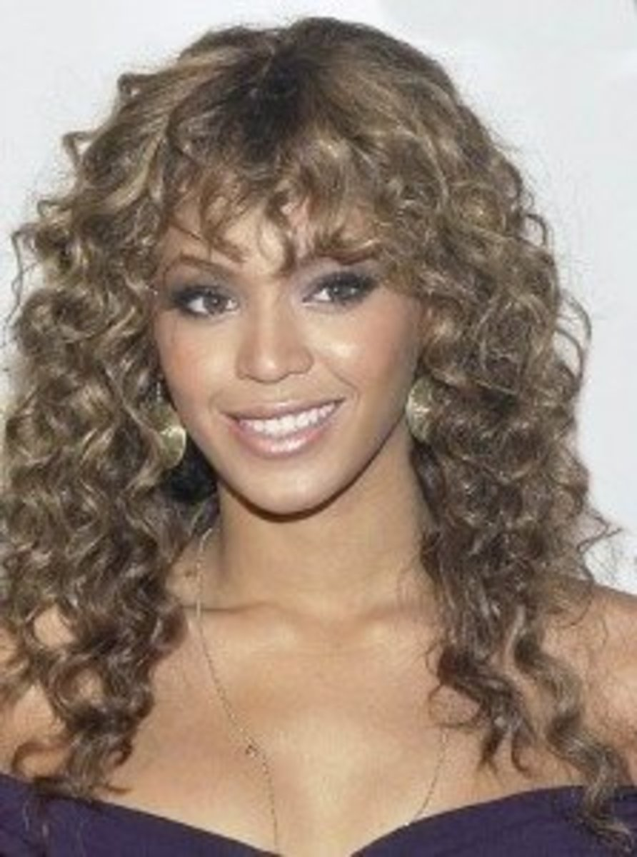 Beyonce with dark ash blonde hair color, in super curly wig with ringlets.