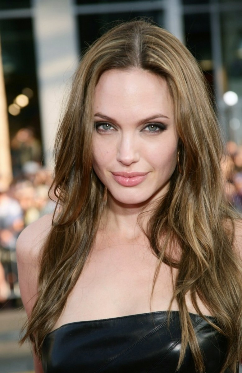 Angelina Jolie with dark ash blonde hair color, long and slightly wavy.