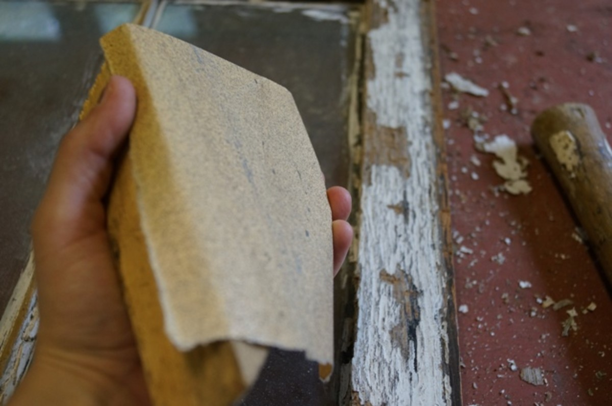 After scraping, sand the remaining paint smooth.  Use a block of wood to rest the sandpaper on, to make it easier to sand.