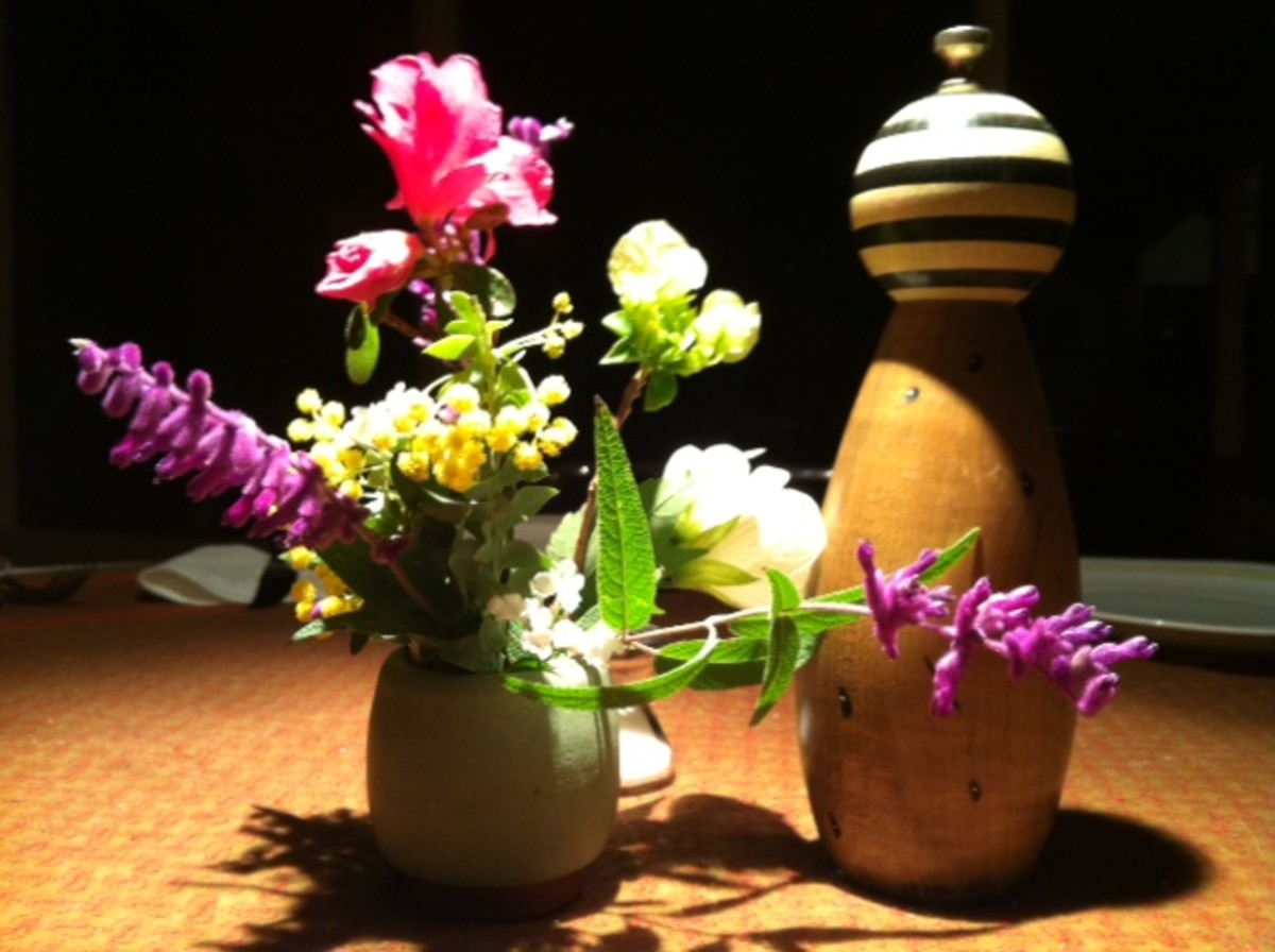 Flowers from a garden in a vase at a dinner party table