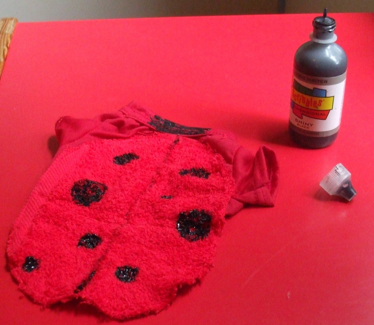 Use a permanent black marker or fabric paint to make ladybug spots on the kitten costume.