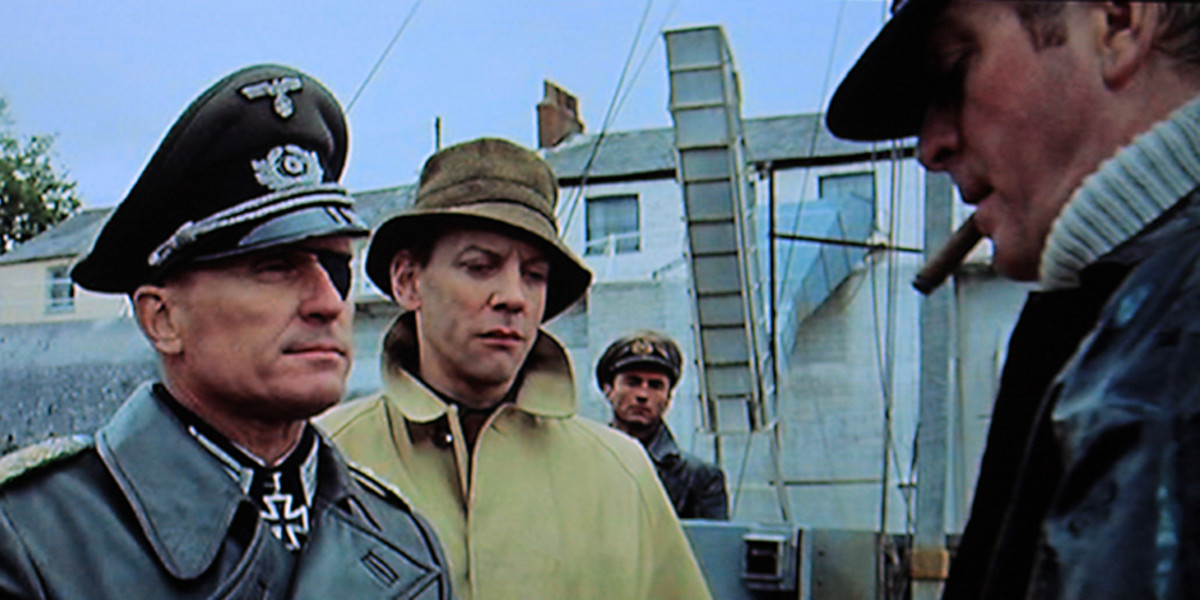 Colonel Radl, accompanied by Liam Devlin (Donald Sutherland), puts forward his proposition to Steiner on the occupied Channel Island of Alderney