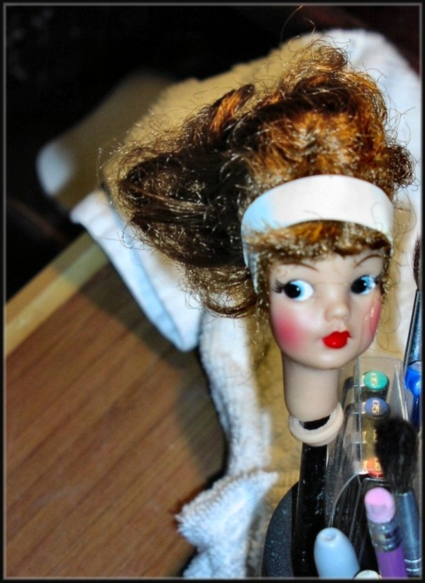 Next, I began to work on the head.  Tammy received a rubber band hair band to set her bangs in place.  The head was propped up with an eraser pen to check out the damage and make sure the head was in a good position to be completely dry.  Glue adhere