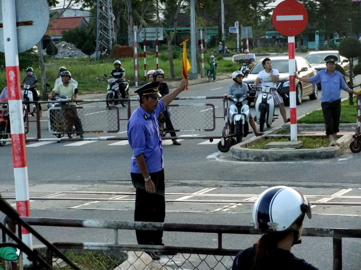 At railway crossing, waiting for the train to pass by, near Danang Vietnam