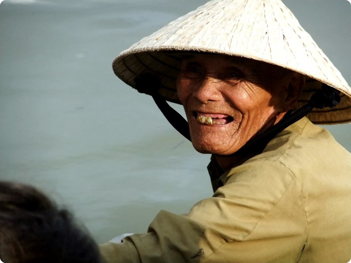 Travel to Hue Vietnam: A boatman wearing the traditional Vietnamese conical hat, waiting for tourist to get onto his boat