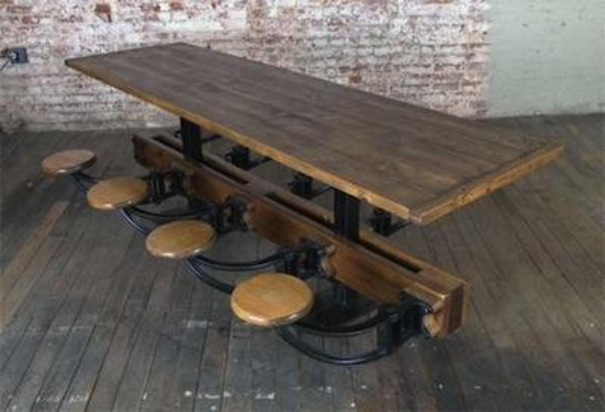 A vintage industrial piece of furniture: a table with slide out stools.