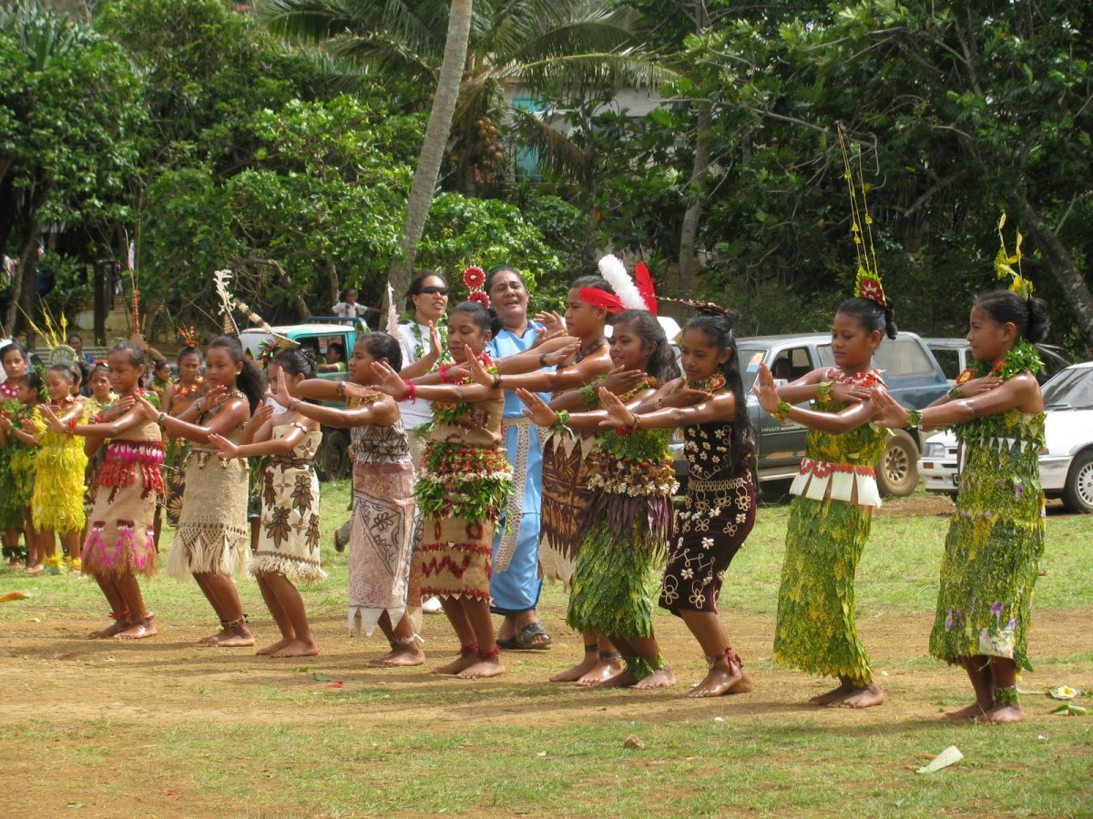 Young girls doing a tau'olunga (dance) with typical costumes.
