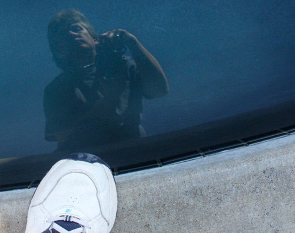 Water is another great reflective surface for self portraits. The water in this swimming pool is a little dark, but you can still see me leaning over to get the shot while also capturing my foot.