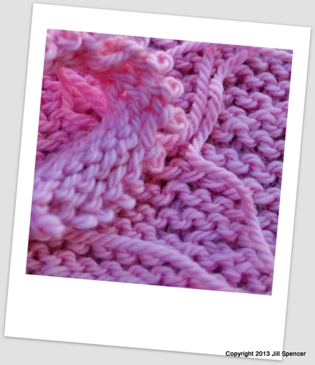 There, huddled on the dirty floormat, was my knitting. A limp, fuzzy mess of purple-pink wool.