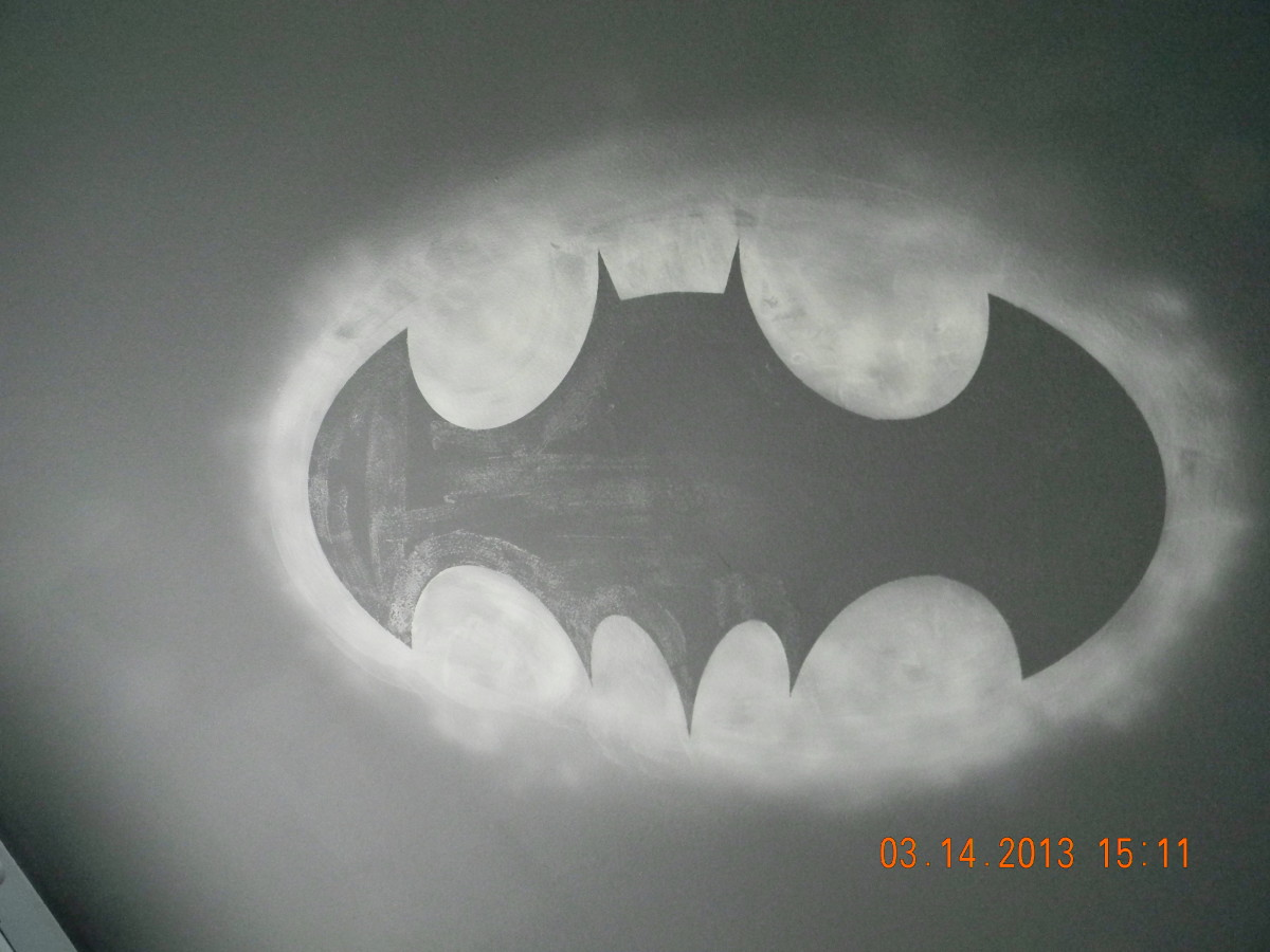 This is the glow in the dark Bat Symbol on the ceiling of the Batman themed bedroom. The outlying oval glows around the black symbol giving the illusion of an actual light being shown on the clouds above. It was produced with Krylon Glowz spray.