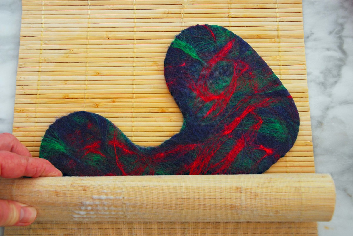 Roll in a Bamboo Mat to complete the fulling process.  It helps shrink the fibers further. Keep on changing the direction of the booties