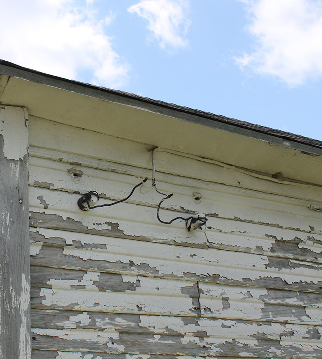 Power lines would come into the home connected with insulators.  This picture shows newer wiring added.  But the original wiring would of went into the homes through the ceramic tubes located above the insulators.