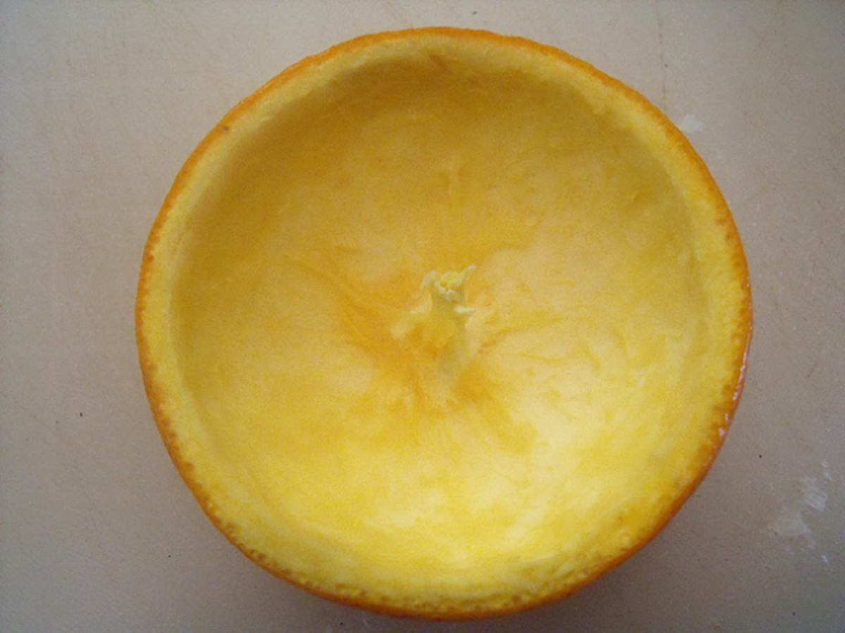 Hollowed out orange peel bowl with a natural wick