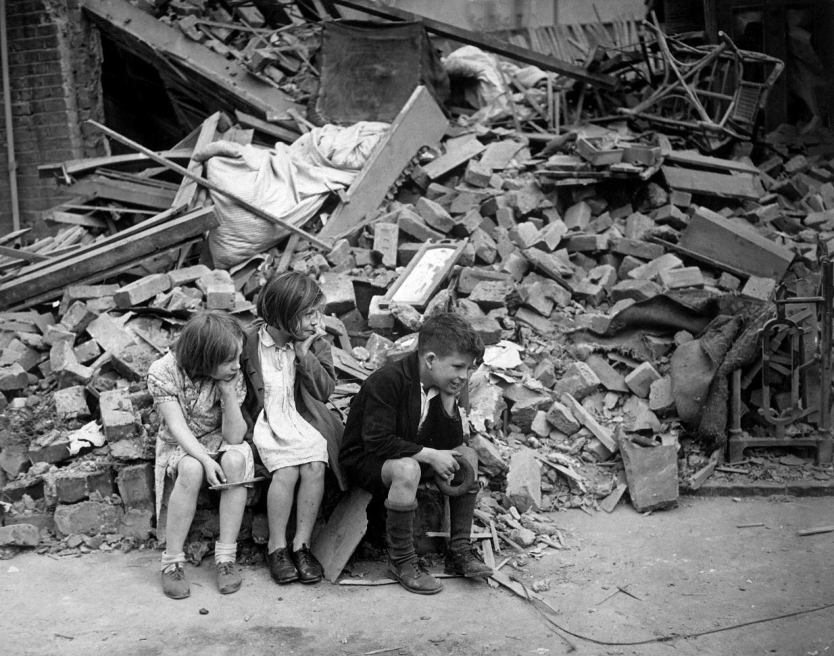 Bombed out children waiting for mother to find them somewhere to shelter