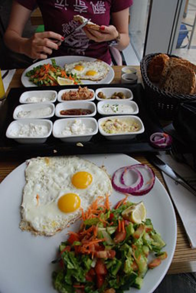 A yummy breakfast of sunny side up eggs and an assortment of cheeses and condiments,