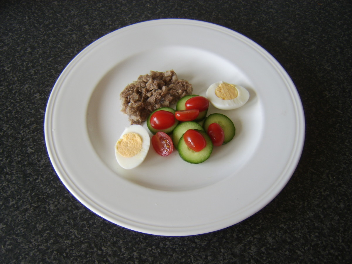 Salad and egg are plated with a thick slice of jellied beef tongue