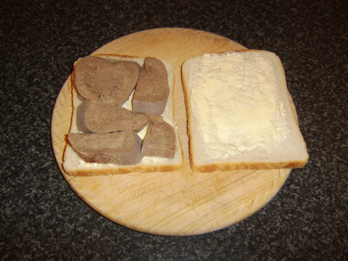 Beef tongue slices are cut to size where necessary and laid on one slice of the bread
