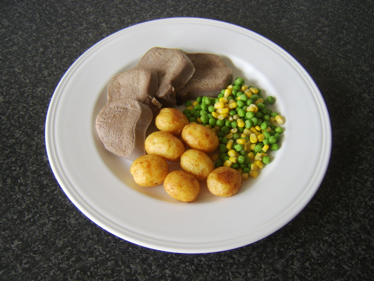 Still warm slices of beef tongue are served with pan roasted baby potatoes and a combination of peas and sweetcorn