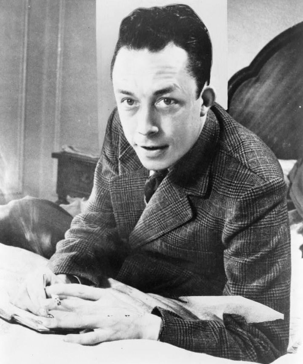Albert Camus, Nobel prize winner, half-length portrait, seated at desk, facing left, smoking cigarette