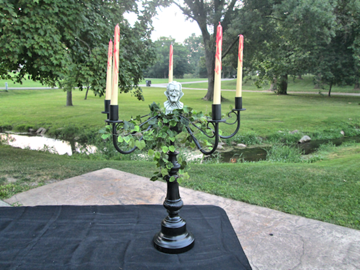 "I added the ivy silk bush in the center and then wound the ""spider"" branches on the arms so that each one had some ivy. I also wound the longest one around the pedestal portion of the holder. Then, just added my vampire figurine to the center and my"