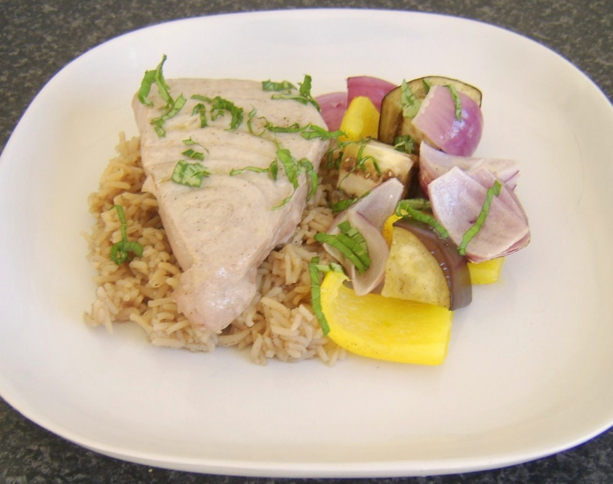 Grilled/broiled tuna fillet on a bed of spicy rice with a Mediterranean vegetable shish kebab