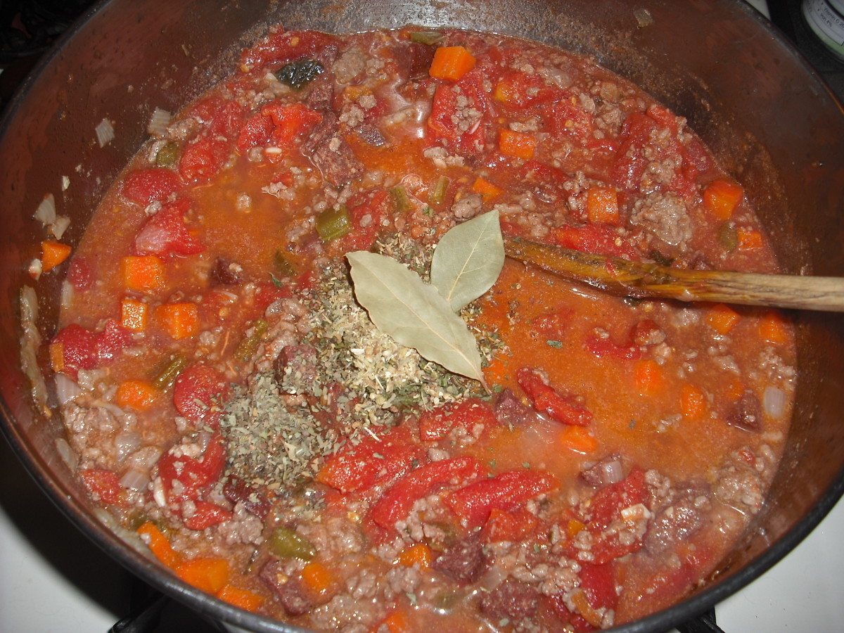 Add the whole tomatoes (crushed with your hands), tomato paste, parsley, basil, oregano and bay leaves.  Stir well.