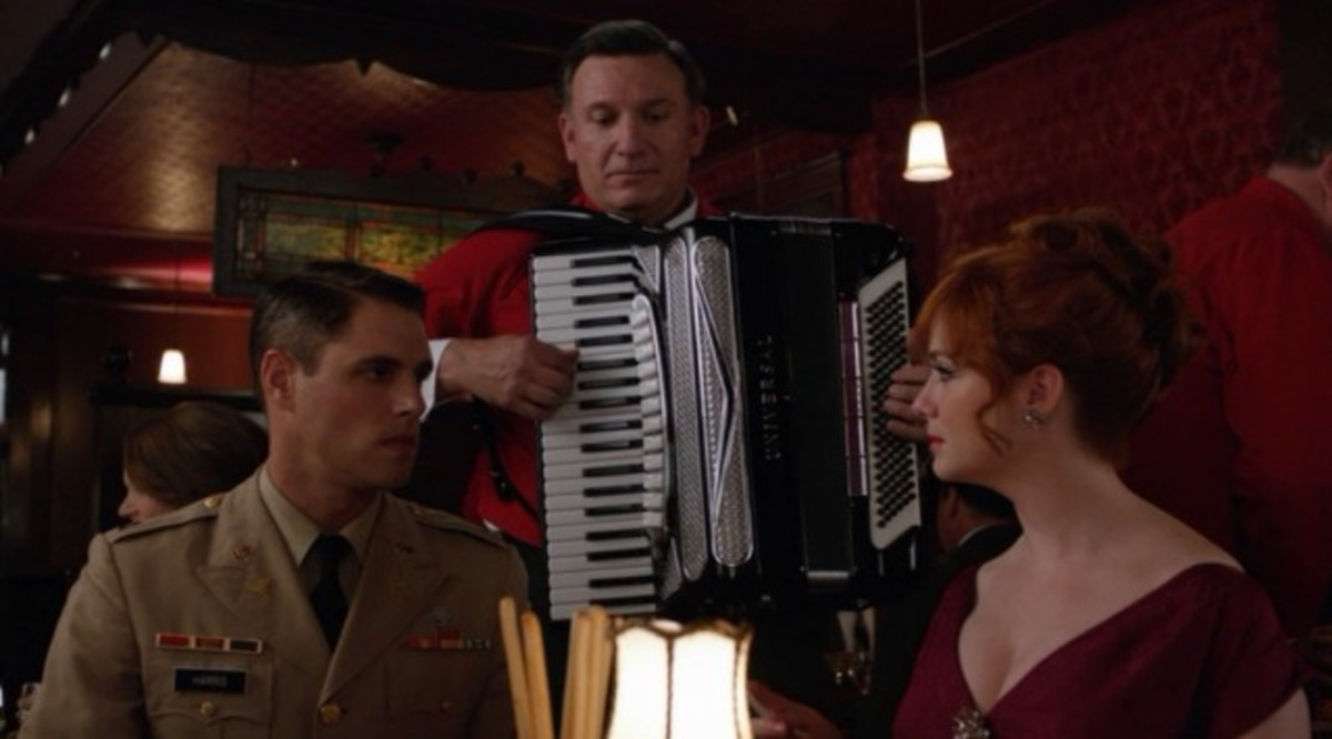 A serious conversation between Greg and Joan is interrupted by accordion music