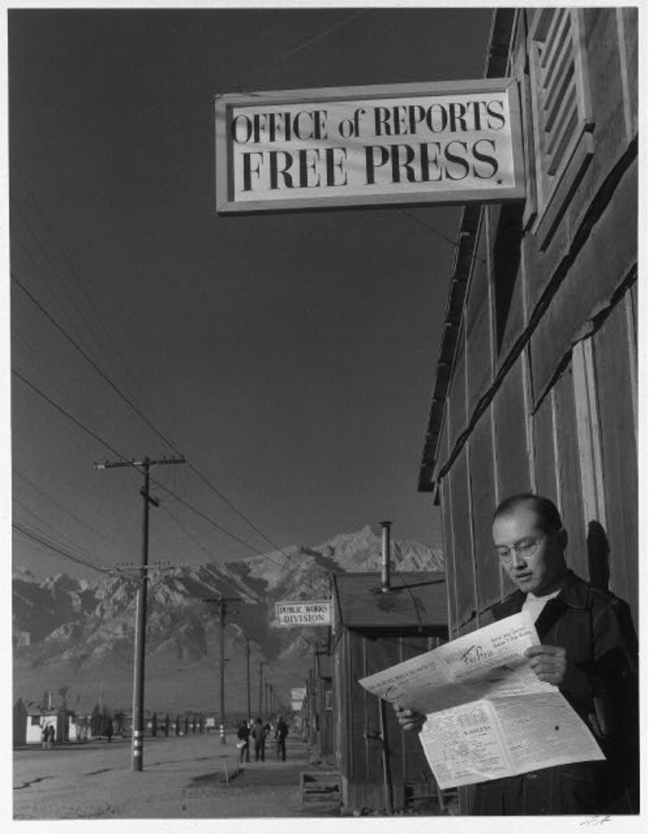 Roy Takeno reading paper in front of office, by Ansel Adams
