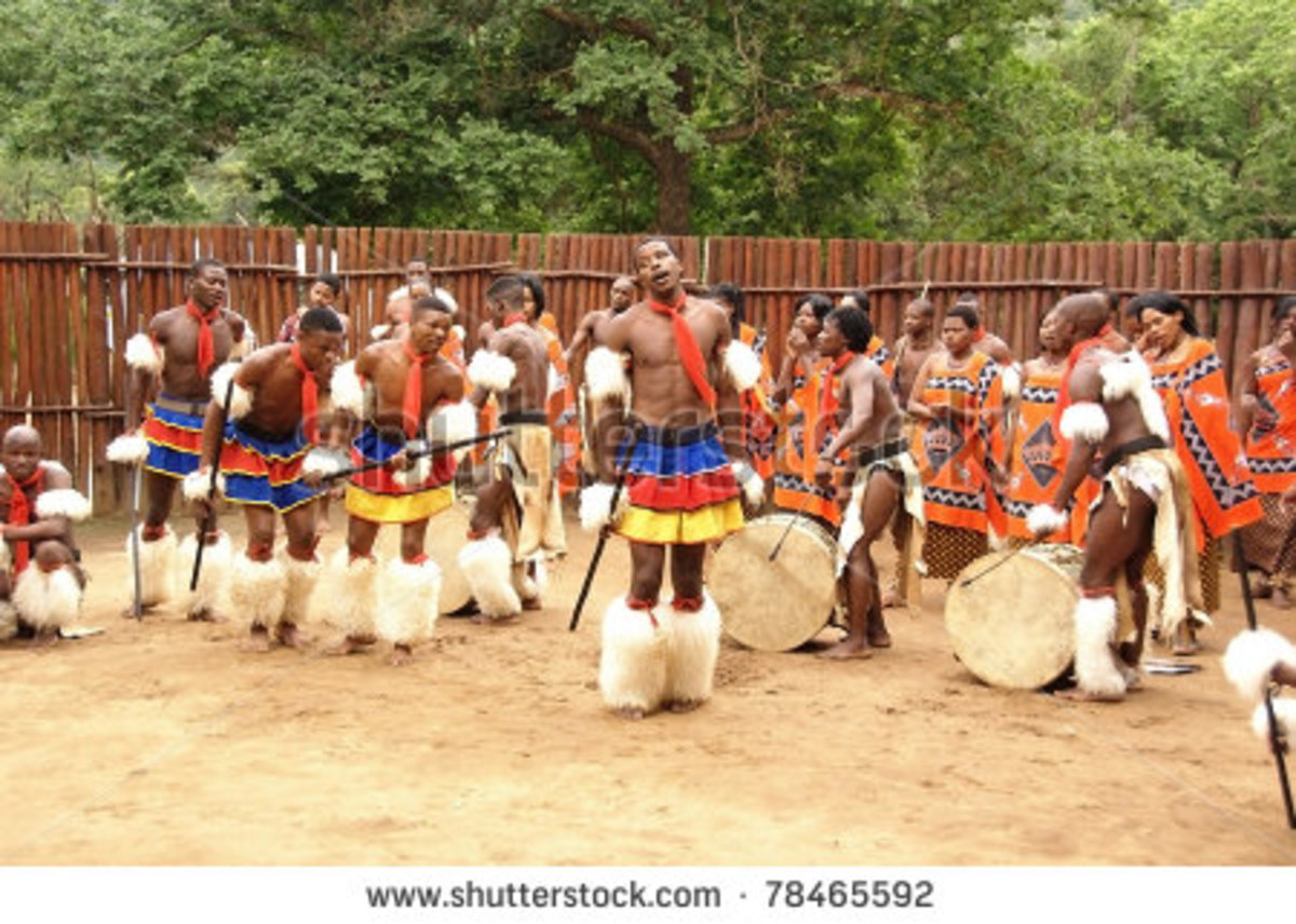 Swazi men and women in the background, in traditional clothes and performing a Swazi traditional dance
