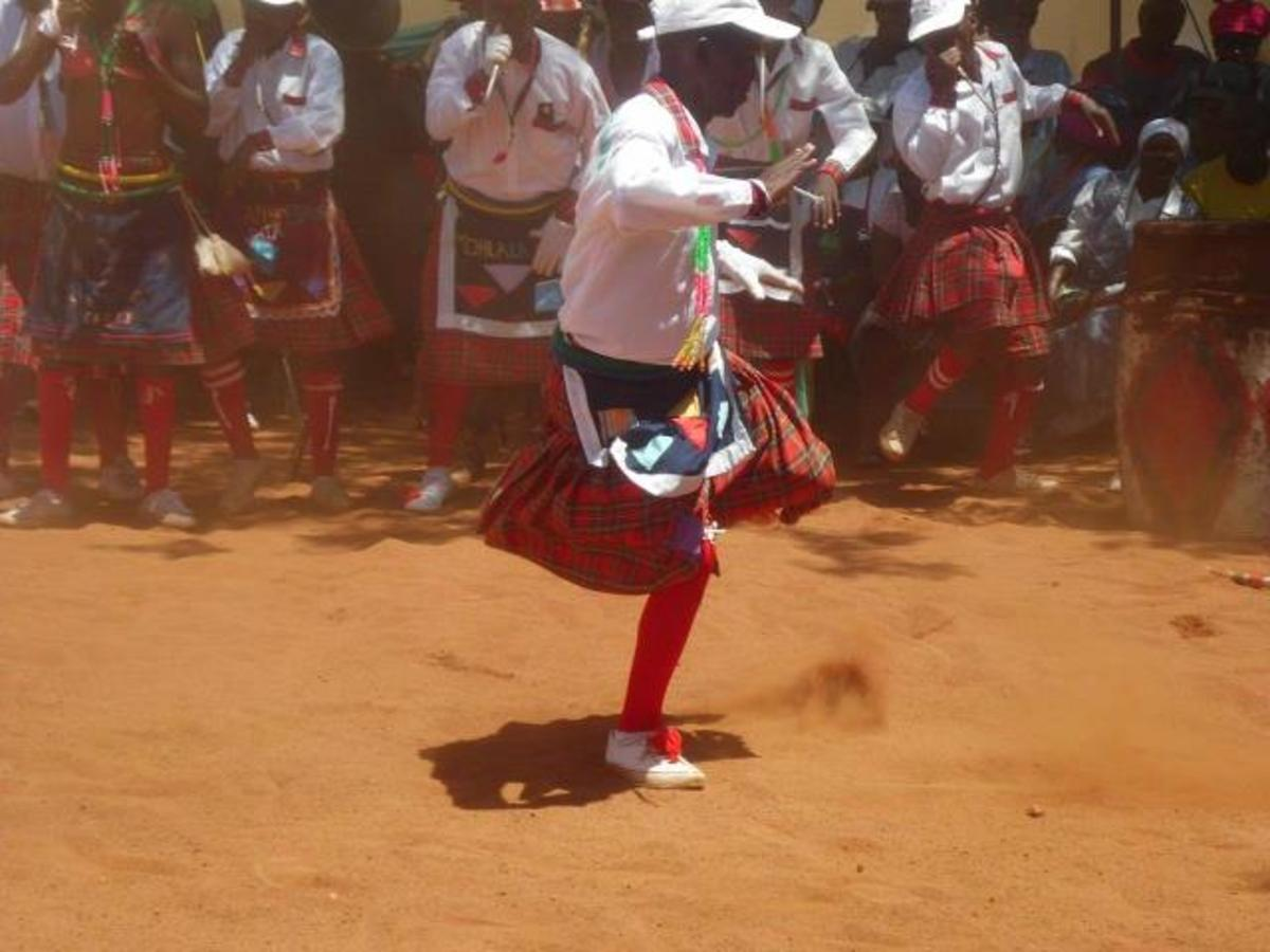 A Mopedi Man in full colorful Bapedi admixture of traditional clothing performing a Pedi traditional dance