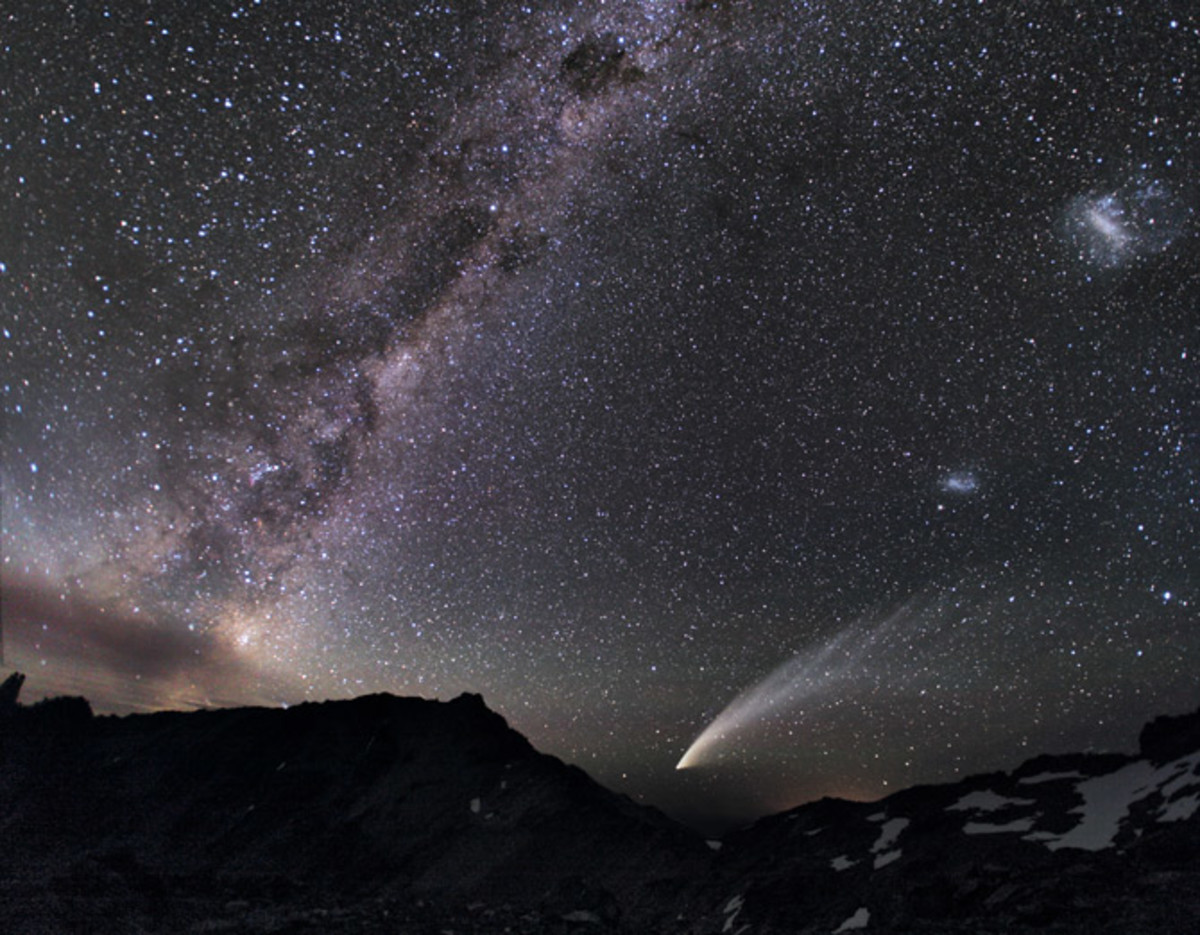 The Magellanic Clouds—two gauzy patches of light (at far right)—share the sky above the Patagonian Andes with a streaking comet and the luminous band of the Milky Way.