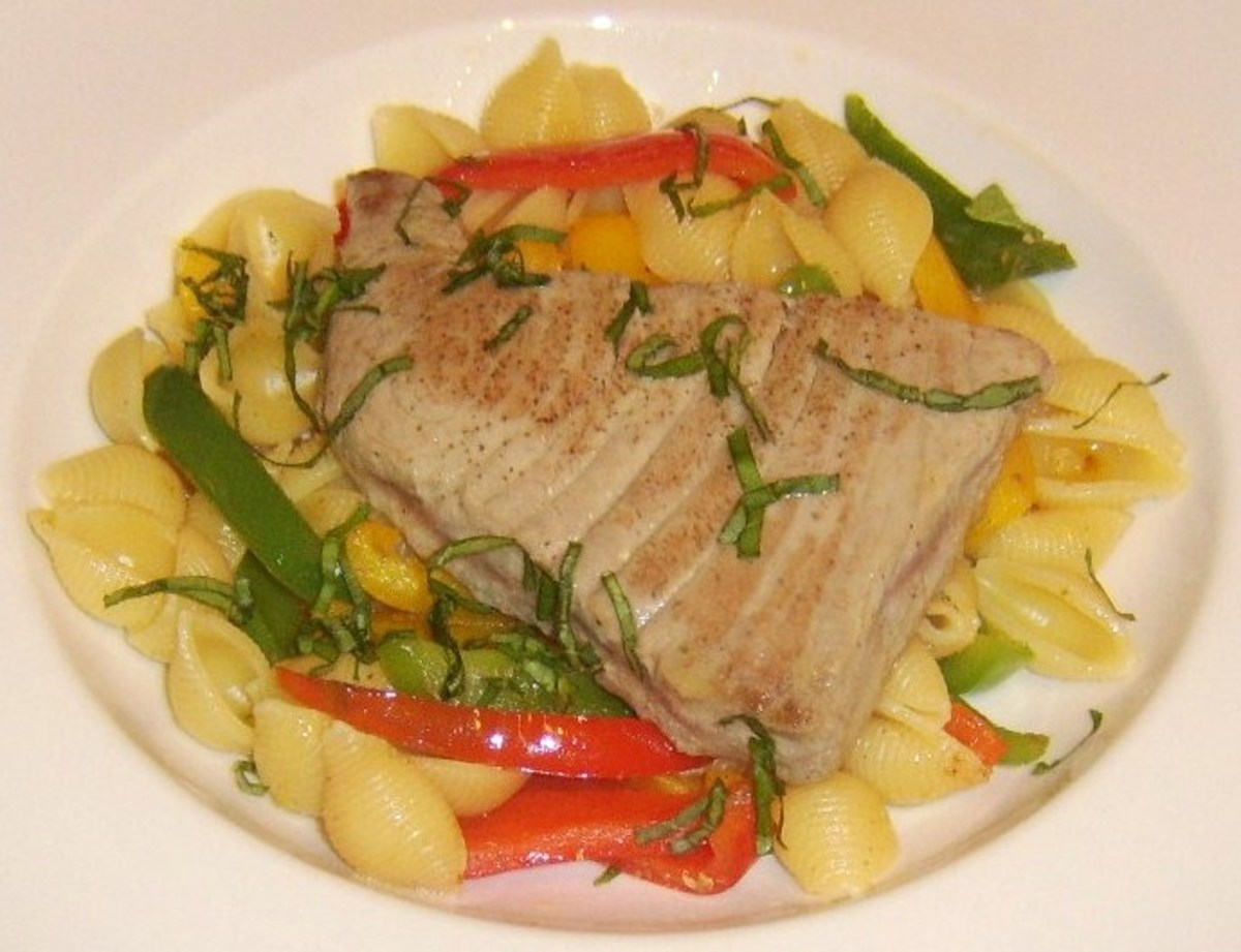A seared tuna steak is served on a bed of conchiglie pasta and mixed bell pepper slices