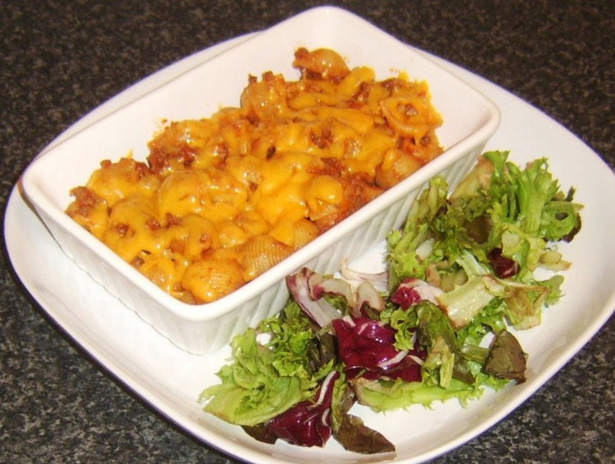 Conchiglie pasta and spicy beef with melted cheese and salad