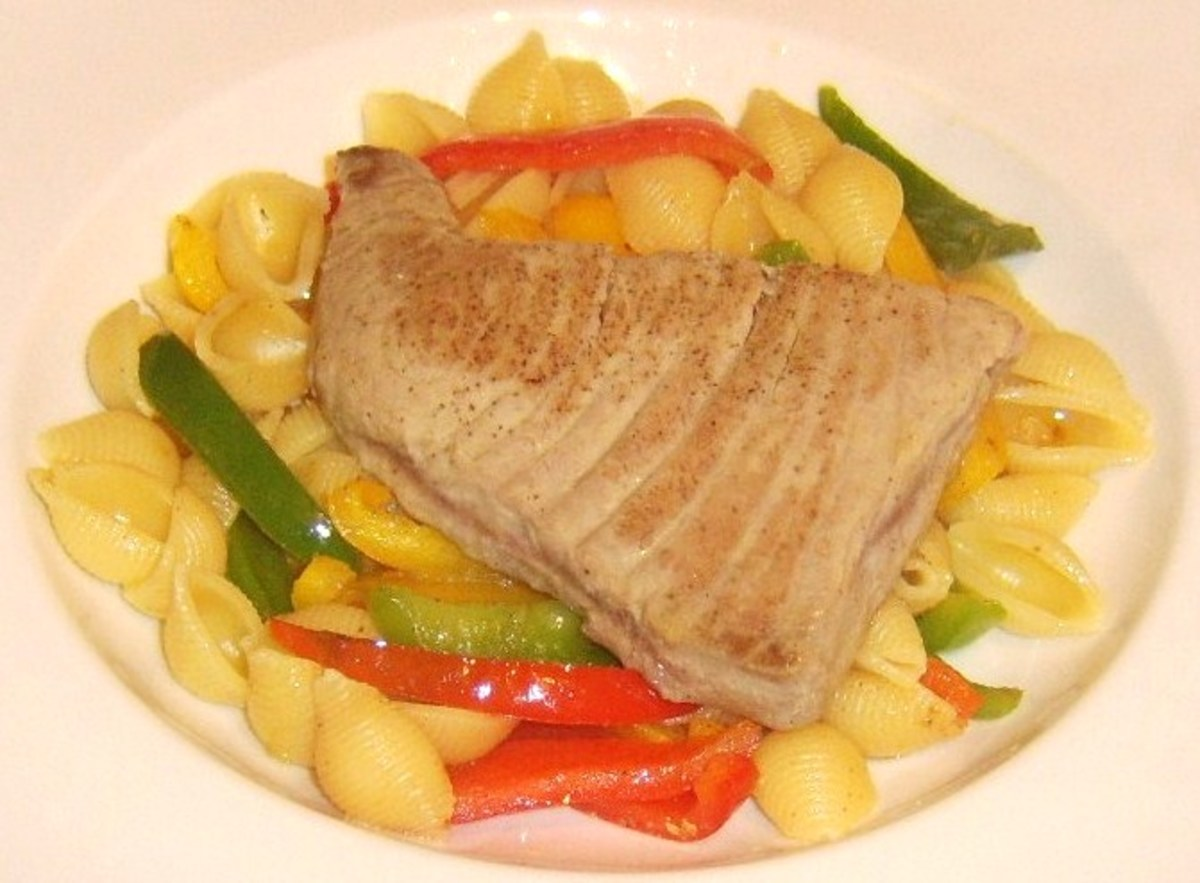 Tuna steak is carefully laid on top of conchiglie and bell peppers