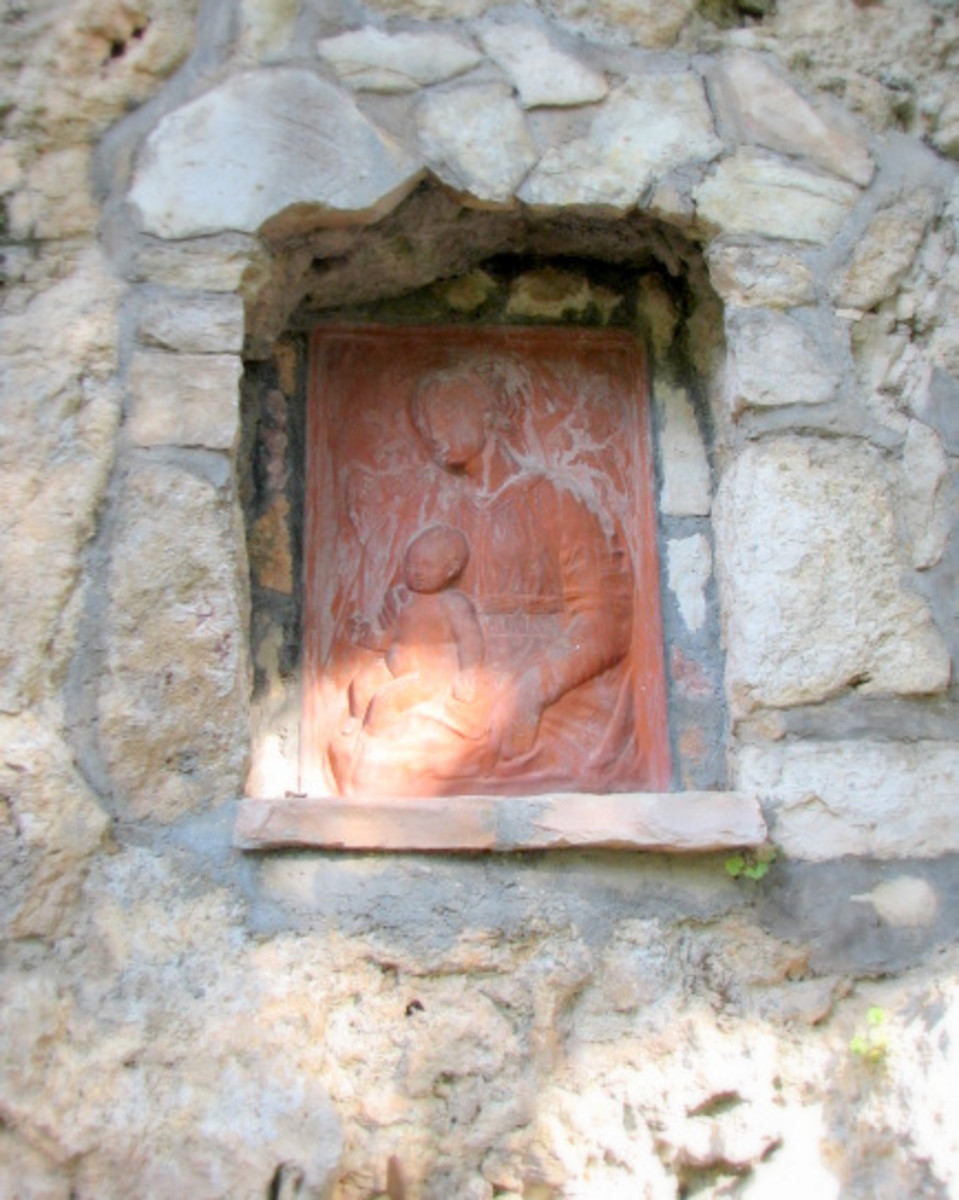 A terra cotta plaque set within a recessed niche of limestone cobbles.