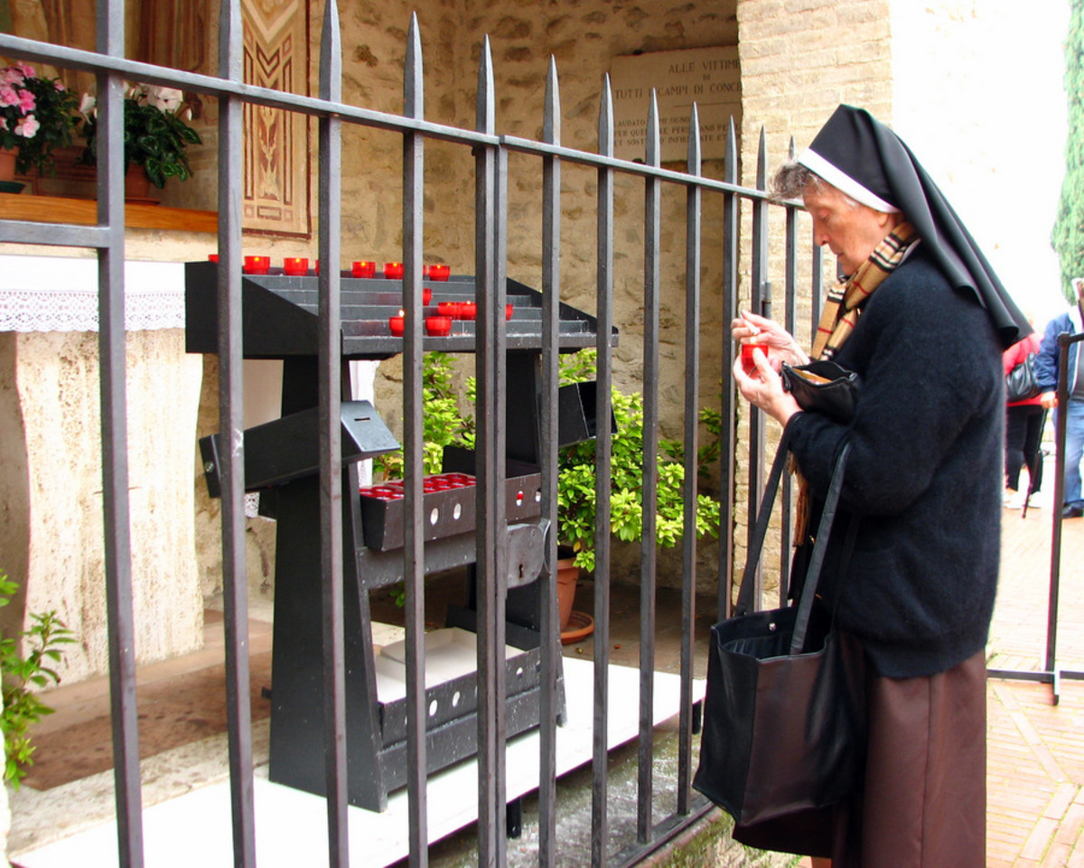 A Franciscan nun lighting a vigil candle at the shrine near the entrance of San Damiano.
